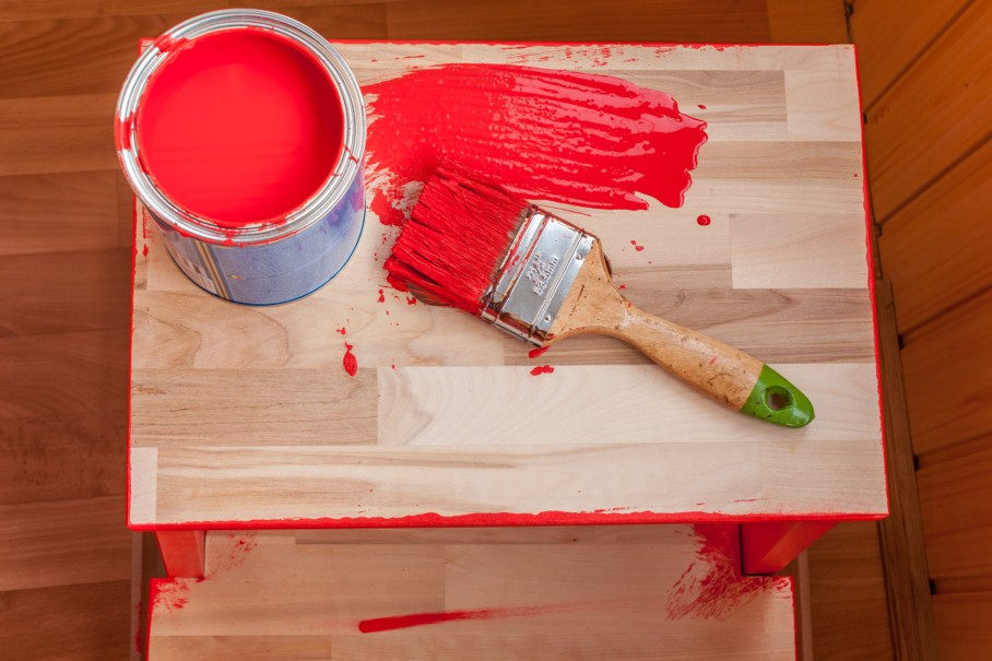 Red paint and brush on wood chair