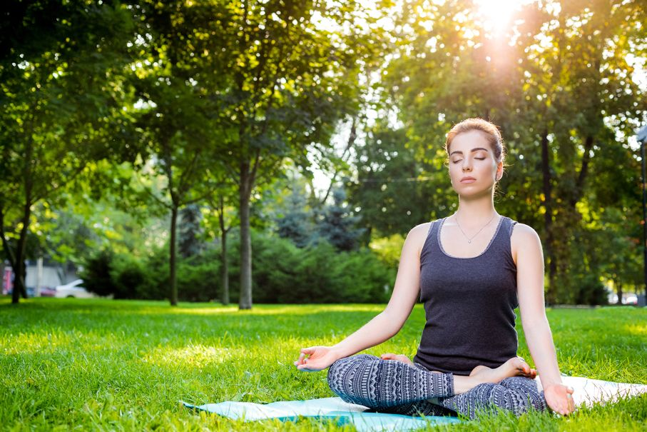 Meditating woman in meditation in city park in yoga pose