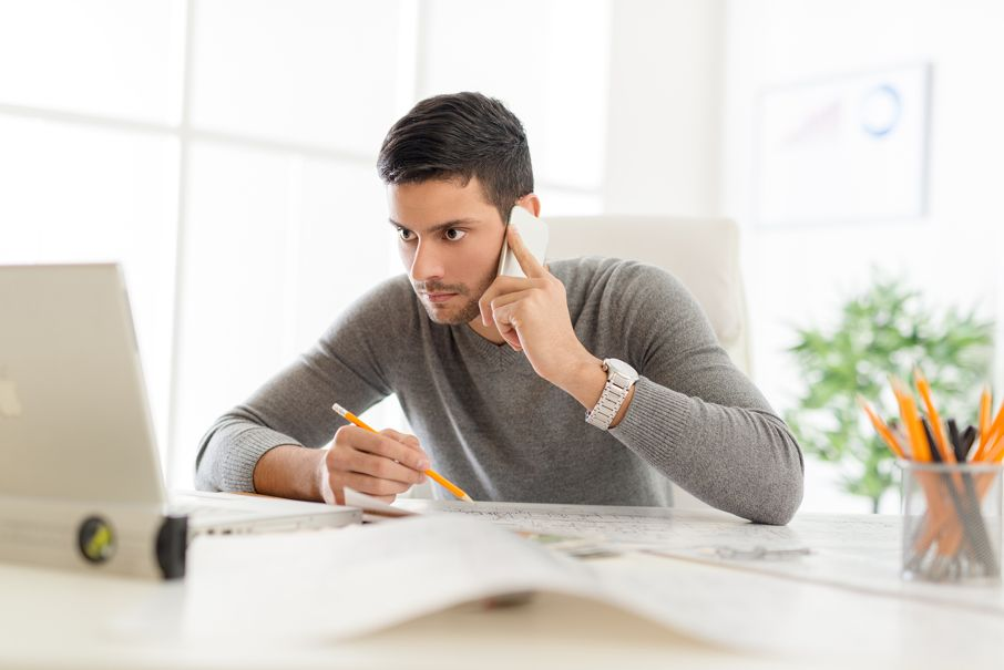 Young contractor sitting at desk in office using phone and analyzing blueprint