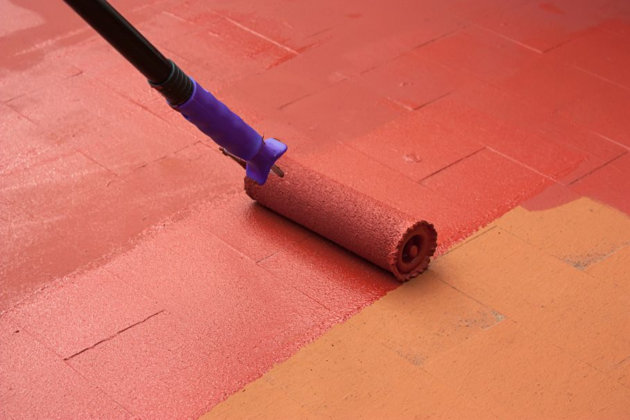 Painter painting a floor on color red