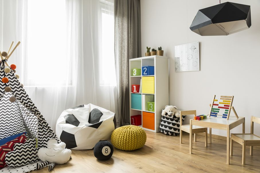 Spacious child room with window play tent sack chair pattern carpet regale sofa small table chairs and new pendant lamp