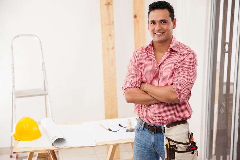 Portrait of a contractor working at a house and smiling