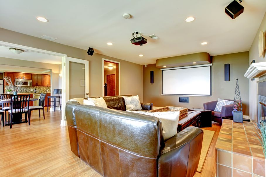 Large living room with brown walls and leather sofa with projector screen