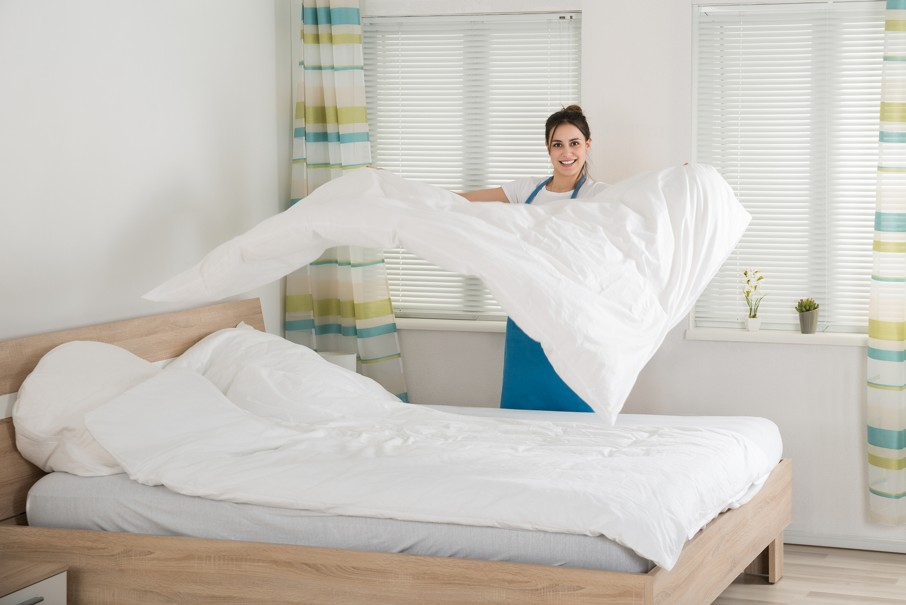 Happy Young Female Housekeeper Changing Bedsheet On Bed In Room