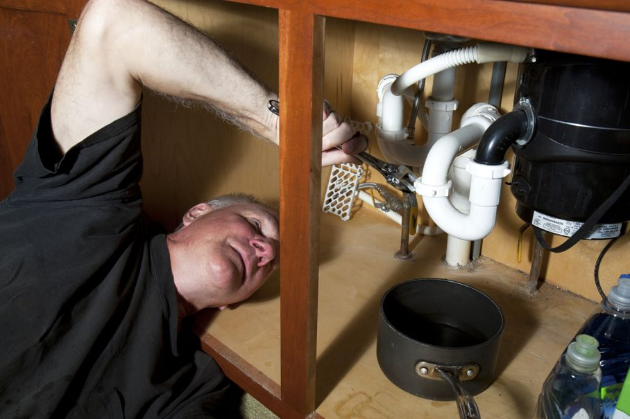 Man with pipe wrench under a kitchen sink fixing a leak