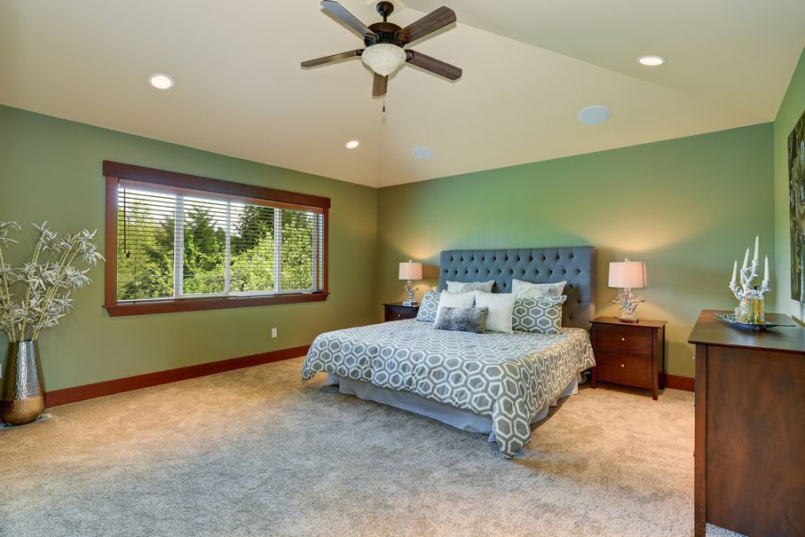 Large bedroom with green interior paint and decorative bedding