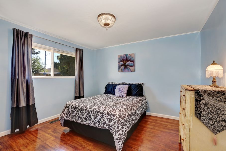 Blue walls bedroom with antique chest of drawers and hardwood floor