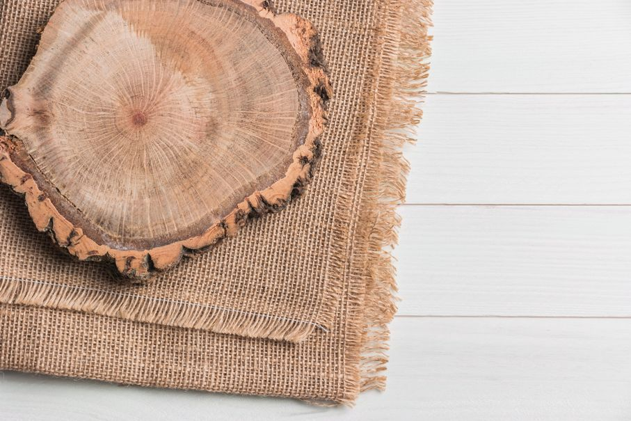 Wood plank board above burlap on wooden table, useful as a background