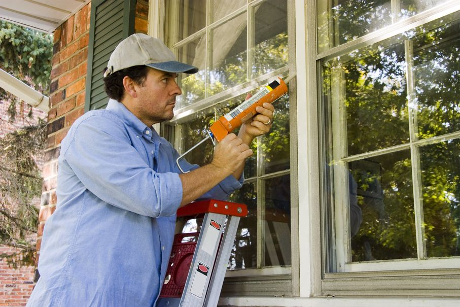 Man on ladder caulking outside window to insulate against the weather