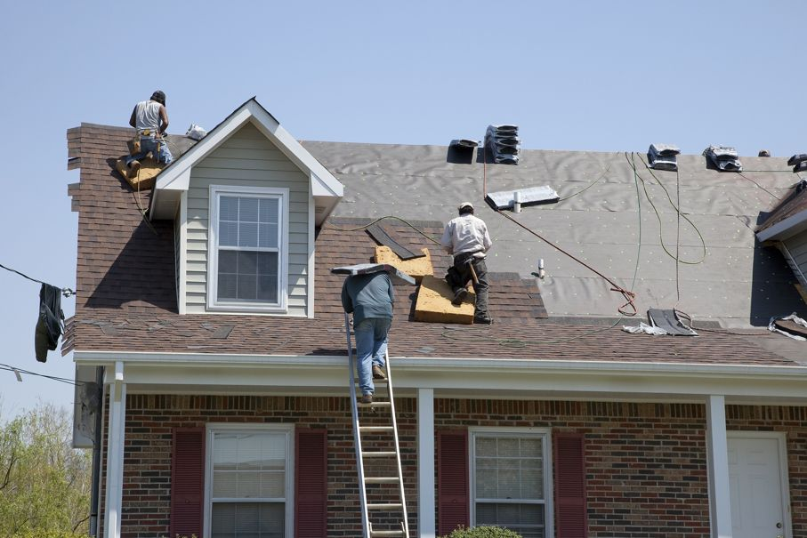 Roofers replacing damaged shingles