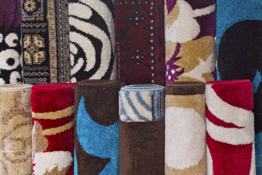 Rugs and carpet floor coverings sold in rolls on a market stall