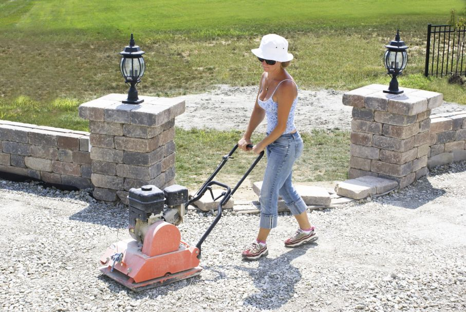 Woman with the white hat compacting patio base under the sun