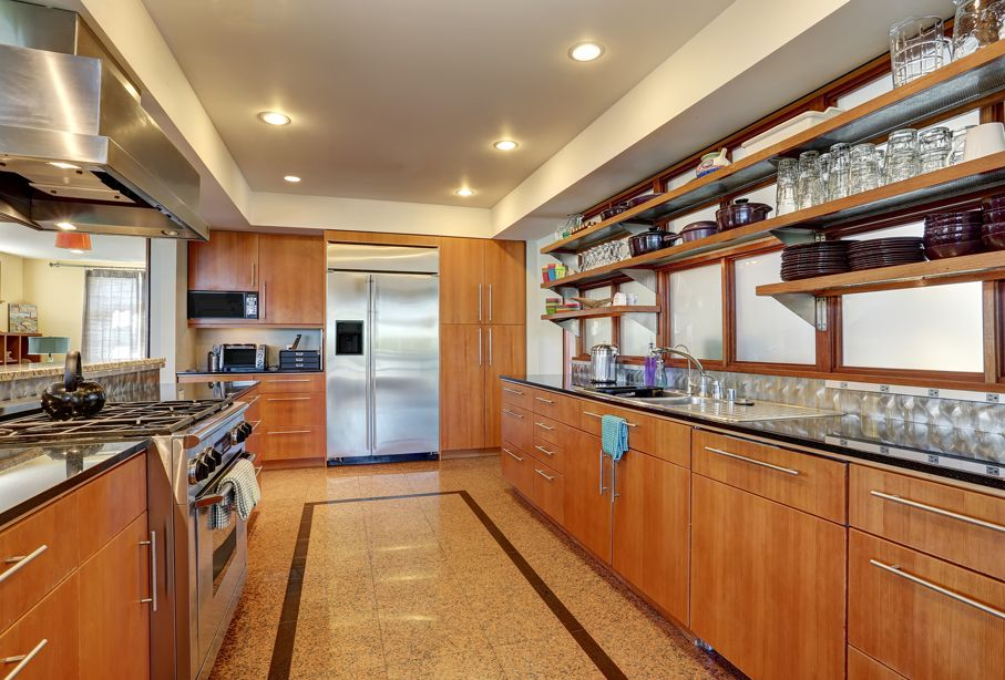 Kitchen interior with long wooden cabinets and shelves