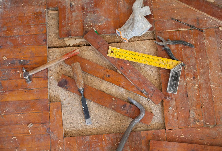 Old rotten parquet floor remove with chisel, hammer tools