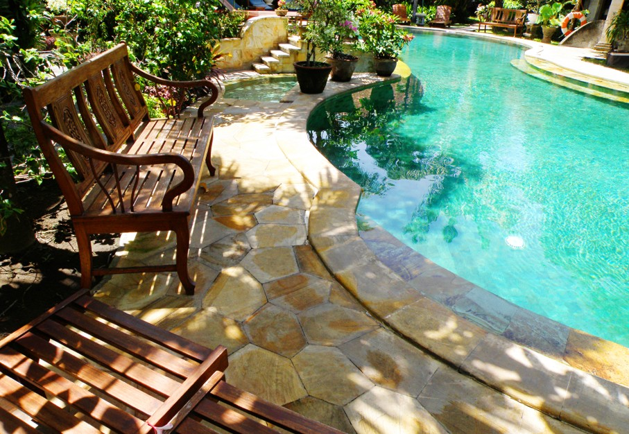 An image of a swimming pool with outdoor poolside patio furniture