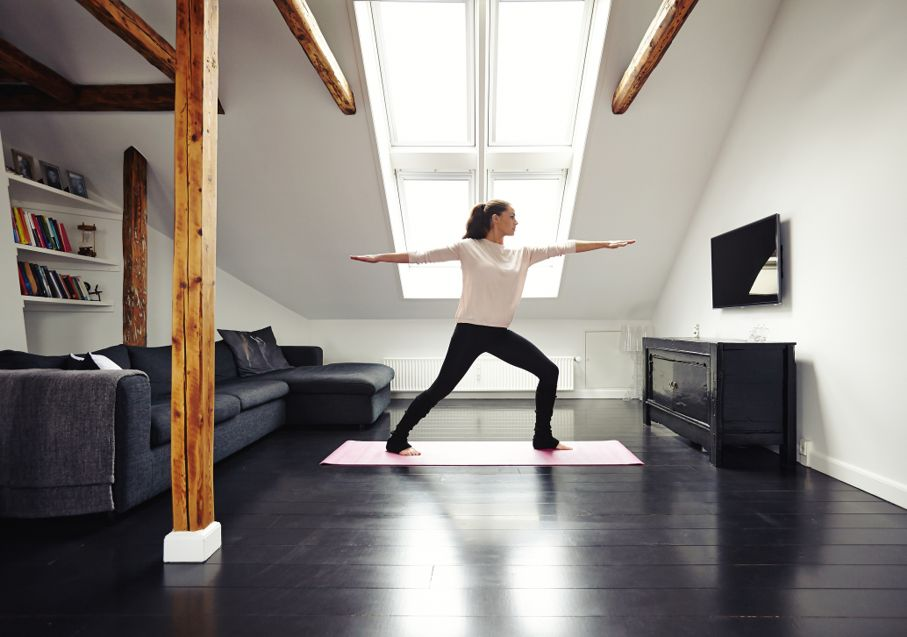 Ffit woman standing on exercise mat with arms outstretched doing yoga in loving room