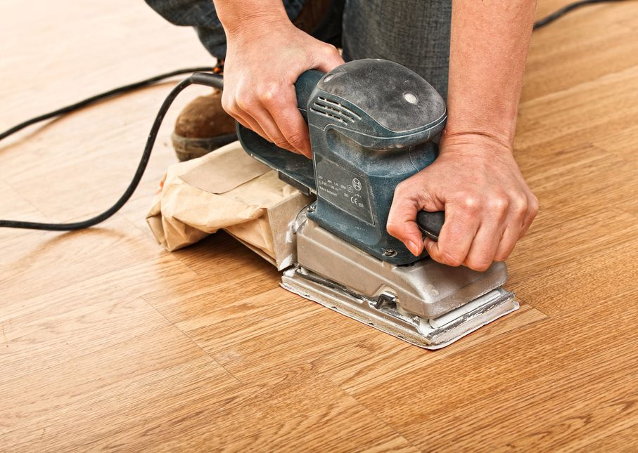 Carpenter use sander on wood floor