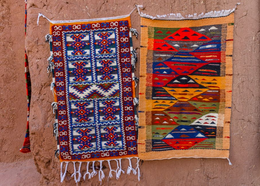 Colorful Moroccan Berber carpets hanging on adobe wall