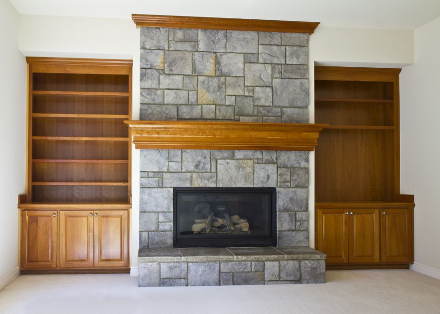 Stone Fireplace with book shelves on white wall