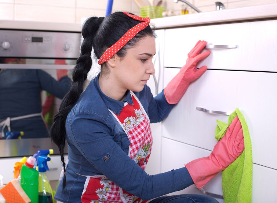 Pretty young woman wiping kitchen cabinets with green cloth