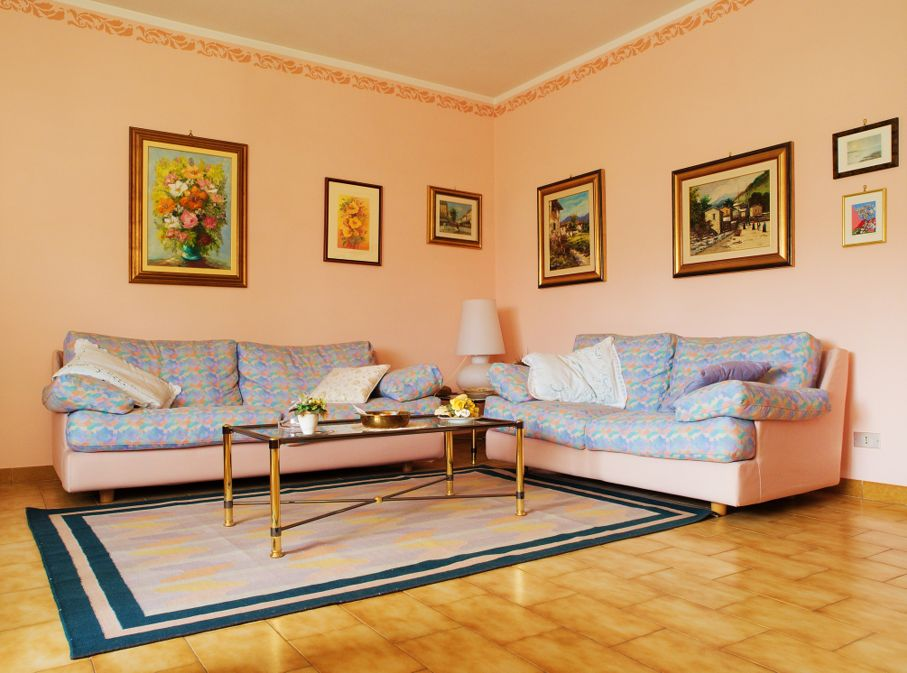A classic living room with carpet, sofas and paintings