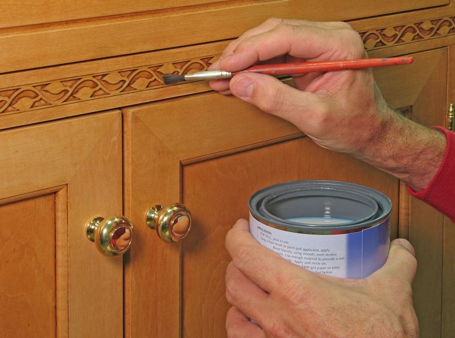 Closeup of painter apply vanish to the inlaid trim