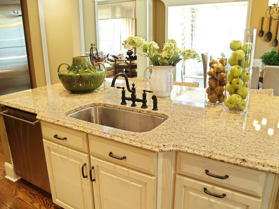 A granite topped island counter in a modern kitchen with dark hardware