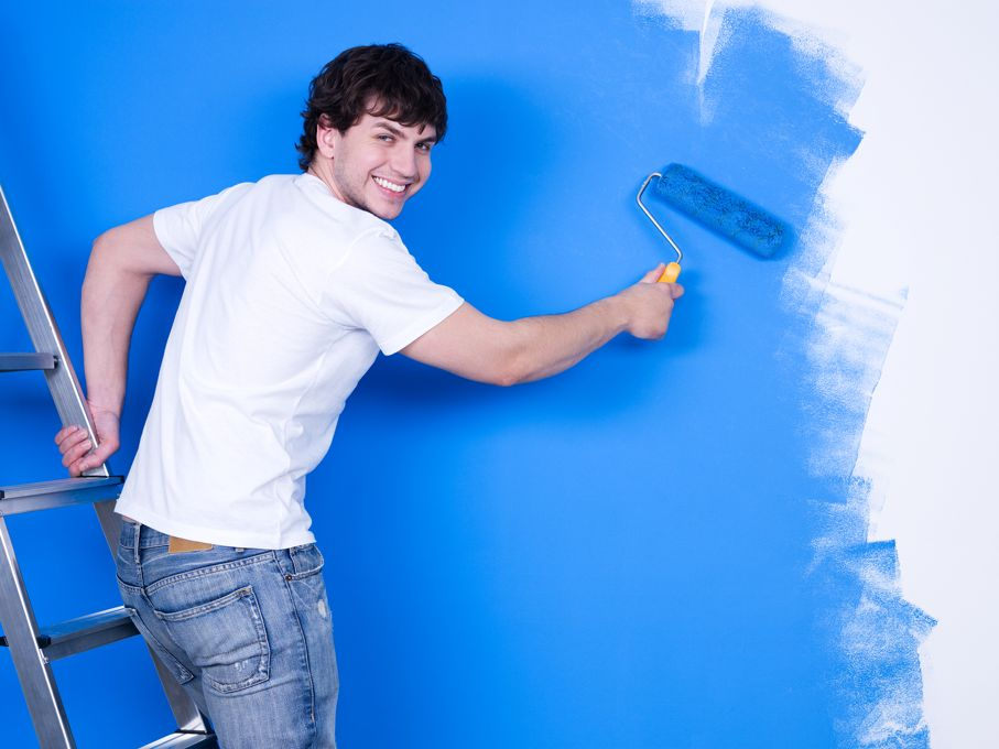 Young man with happy smile painting the wall