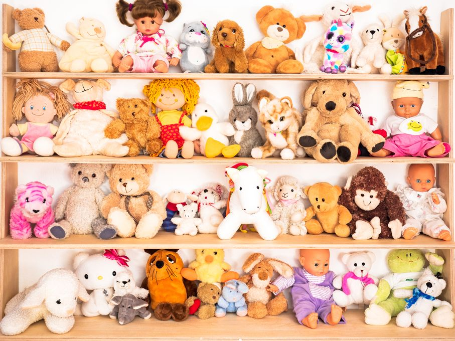 Many stuffed animals and dolls on the shelf
