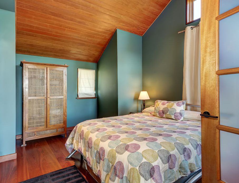 Cosy green and blue upstairs bedroom with minimal design and wardrobe