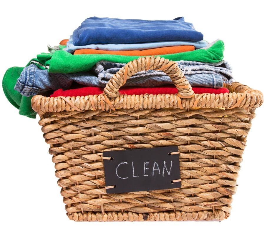 Wicker laundry basket filled with stack of folded colorful clean clothes ready for ironing with a handwritten label on the side of the basket saying - Clean